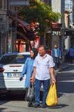 Istambul, TURQUIA, o 20 de setembro de 2018 Família muçulmana feliz que anda abaixo da rua com os sacos de compras da loja imagens de stock