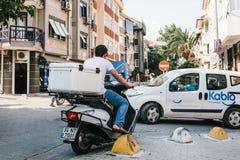 Istanboel, 14 Juni, 2017: Achtermening - niet geïdentificeerde bestuurderszitting achter het wiel van kleine bromfiets met witte  royalty-vrije stock afbeeldingen