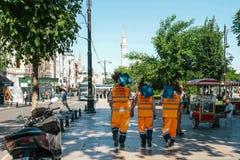 Istanboel, 15 Juni, 2017: Drie straatportiers in heldere oranje uniformen lopen onderaan de bezems van de straatholding en royalty-vrije stock afbeeldingen