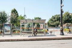 Istanboel, 15 Juni, 2017: Het eenzame bejaarde sitiing op een bank bij het busstation die van Sultanahmet op vervoer wachten stock afbeelding