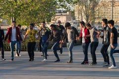 """Istanboel, Turkije †""""28 April, 2018: de jonge kerels dansen aan nationale muziek op de Bosphorus-dijk in het district van Ãœskà stock afbeelding"""