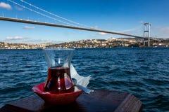 Istanboel, Turkije 12-november-2018 Turks rood theeglas voor Bosphorus-rivier en Ortakoy-brug als achtergrond stock foto's