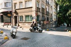 Istanbuł, Czerwiec 14, 2017: Dwa ludzie jadą moped past pusty parkujący moped w Istanbuł na ciepłym letnim dniu Zdjęcie Stock