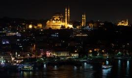 Istanbuł linia horyzontu od Galata mosta nocą, z Suleymaniye meczetem i ryba łódkowatymi restauracjami w Eminonu Fotografia Royalty Free
