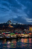 Istanbul. Skyline from Galata bridge by night, with Suleymaniye mosque and fish boat restaurants in Eminonu Stock Photo