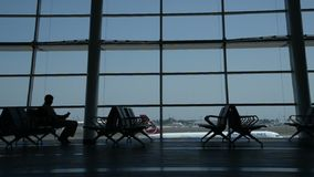 Istanbul Ataturk Airport background. A silhouette man reading a newspaper and a plane passing out. Istanbul, Turkey - July 7, 2017: Istanbul Ataturk Airport stock video footage