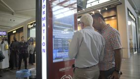Istanbul Ataturk Airport 15 October 2015 - Men checking flight timetable at modern touchscreen info kiosk stock video footage