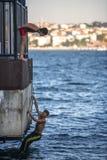 ISTANBUL - 5. AUGUST: Jugendliche springen in Bosphorus-Meer vom Holz Stockfoto