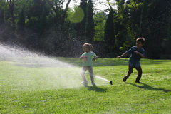 Istanbul - August 28, 2014. Two kids playing with the Sprinkler, Sultanahmet park, Istanbul, Turkey Stock Photography