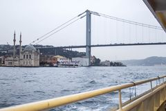 Istanbul bridge and mosque from river boat in cloudy afternoon. royalty free stock photo