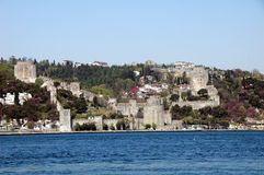 Istanbul Castle. Rumeli Hisari Castle in Istanbul, Turkey on mountainous shore, blue water in foreground stock photo