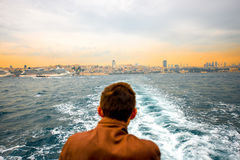 """Istanbul city line. ISTANBUL -€"""" MAY 29, 2015: Turkish man looks on the Istanbul cityscape from the ferry floating to the Princes island in the morning Stock Photo"""
