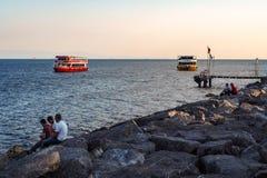 ISTANBUL, DIE TÜRKEI - 21. AUGUST 2018: Leute entspannen sich auf Steinen auf Seeufer, Boote lizenzfreies stockbild