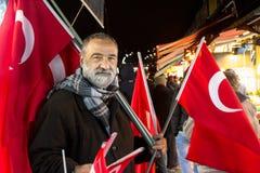 ISTANBUL, DIE TÜRKEI - 30. DEZEMBER 2015: Alter Mann, der türkische Flaggen auf dem europäischen Teil von Istanbul verkauft Lizenzfreie Stockfotos