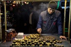 ISTANBUL, DIE TÜRKEI - 28. DEZEMBER 2015: Bild eines jungen Kastanienverkäufers an einem kalten Winterabend auf Istiklal-Straße Stockfotos