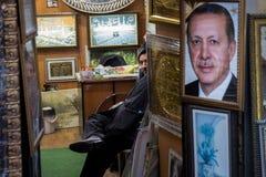 ISTANBUL, DIE TÜRKEI - 29. DEZEMBER 2015: Ladenbesitzer, der ein enormes Porträt des türkischen Präsidenten, Recep Tayyip Erdogan Lizenzfreie Stockbilder