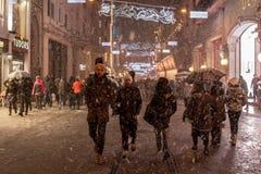 ISTANBUL, DIE TÜRKEI - 30. DEZEMBER 2015: Leute, die unter einen Schneesturm auf Istiklal-Straße, Hauptfußgängerstraße von Istanb Lizenzfreie Stockfotos