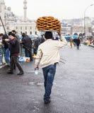 ISTANBUL, DIE TÜRKEI - DEZEMBER, 29 2009: Nicht identifizierter Straßenhändler, der simits auf einem Straße nahe gelegenen Eminon Stockfotografie