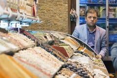 Istanbul, die Türkei - 04/22/2016: Ein Verkäufer, der türkische Gewürze im großartigen Gewürz-Basar verkauft Bunte Gewürze in den lizenzfreie stockfotografie
