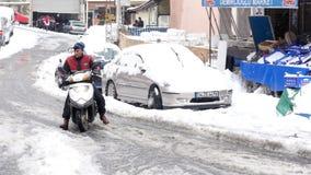 ISTANBUL, DIE TÜRKEI - FEBRUAR 2015: Rollerkurierreiten, schneebedeckte Straßen