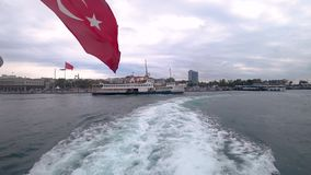 Istanbul ferry departing from Kadikoy pier into bosphorus with waving Turkish flag. Istanbul, Turkey - May 2018: istanbul ferry departing from Kadikoy pier into stock video footage