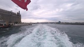 Istanbul ferry sailing by the famous Haydarpasa train station with waving Turkish flag stock footage