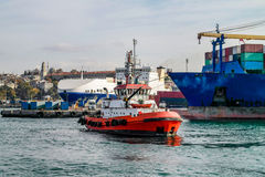 Istanbul fire boat. In front of cargo ships Stock Photo
