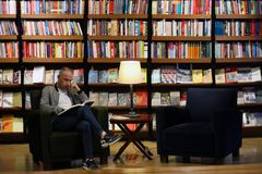 Istanbul Istiklal gata/Turkiet 9 5 2019: Salta Beyoglu Art Center, män som framme läser en bok av bokhyllan royaltyfria bilder