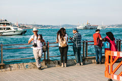 Istanbul, June 15, 2017: Elderly photographer and two young people on the pier. Turkey. In the background is the Stock Photography