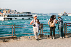 Istanbul, June 15, 2017: Elderly photographer and two young people on the pier. Turkey. In the background is the Stock Images