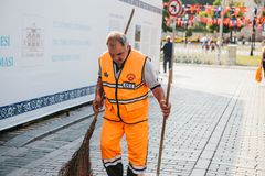 Istanbul, June 15, 2017: janitor in bright orange uniform sweeping the tile on the street in Sultanahmet district. Janitor in bright orange uniform sweeping the Stock Photos