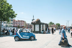 Istanbul, June 15 2017: Municipal tourist team. Blue Smart car and people at Eminonu square in the middle of the day. Editorial image of small blue Smart car Stock Images