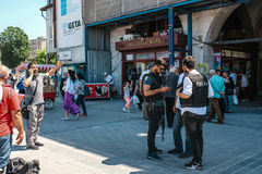 Istanbul, June 15 2017: People at Eminonu Square in the middle of the day - police officers, man talking on the phone. Editorial image of people at Eminonu Stock Photo