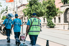 Istanbul, June 15, 2017: Three street janitors in uniforms are walking down the street holding brooms and dust pans. Royalty Free Stock Photos