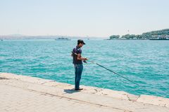 Istanbul, June 17, 2017: Traditional Turkish fishing hobby. A local fisherman is fishing on the shore. Ordinary life in. Turkey Royalty Free Stock Photography