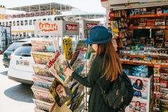 Istanbul Juni 17, 2017: Den unga härliga flickan i en hatt med en ryggsäck köper en tidskrift eller en tidning i en gatapress Arkivbild
