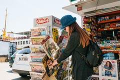 Istanbul Juni 17, 2017: Den unga härliga flickan i en hatt med en ryggsäck köper en tidskrift eller en tidning i en gatapress Royaltyfria Foton