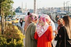 Istanbul Juni 15, 2017: Islamiska kvinnor i traditionell dress meddelar med de och väntar på en taxi på Arkivbild