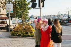 Istanbul Juni 15, 2017: Islamiska kvinnor i traditionell dress meddelar med de och väntar på en taxi på Royaltyfri Foto