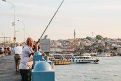 Istanbul, le 15 juin 2017 : Un pêcheur de la population locale se tient sur le pont et les poissons de Galata Passe-temps traditi Photo libre de droits