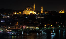 Istanbul skyline from Galata bridge by night, with Suleymaniye mosque and fish boat restaurants in Eminonu Royalty Free Stock Photography