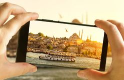Istanbul at sunset, Turkey. Taking photo of Golden Horn by cell phone. Tourist boat sails in the Istanbul center. Sunny picture of eastern landscape on stock photo