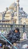 Istanbul, Turkey / April 1, 2016 - Man sleeps while fishing off the bridge royalty free stock images