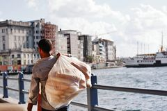Man carrying bread (ekmek) on Galata Bridge, Istanbul. Istanbul, Turkey, 10 August 2018. Man carrying bread (ekmek) in a bag on Galata Bridge in Istanbul. In the stock photo