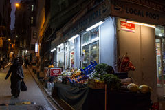 ISTANBUL, TURKEY - DECEMBER 28, 2015: Food shop on a typical street of Galata in the evening, a veiled woman passing by Stock Photography