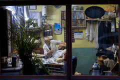 ISTANBUL, TURKEY - DECEMBER 29, 2015: Old barber shaving one of his client at night, in an old fashionned barber shop on the Europ. Picture of an old barber and stock photo