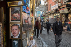 ISTANBUL, TURKEY - DECEMBER 28, 2015: People passing by portraits of Kemal Ataturk and Recep Tayyip Erdogan, current president of. Picture of men passing next to Royalty Free Stock Image