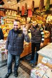 Istanbul, Turkey-December 14, 2015 -Smiling Turkish men in blue uniform. Trade in the market with oriental sweets - nuts, dried fruits, pastilles and other Stock Photos