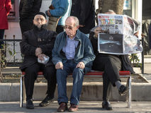 ISTANBUL, TURKEY - DECEMBER 28, 2015: Three old Turkish men sitting on a bench near Kadikoy district, on the Asian side of the cit Royalty Free Stock Images