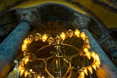 ISTANBUL, TURKEY: Hagia Sophia interior. Old metal chandelier with light bulbs between columns. Hagia Sophia is the greatest monument of Byzantine Culture stock photography